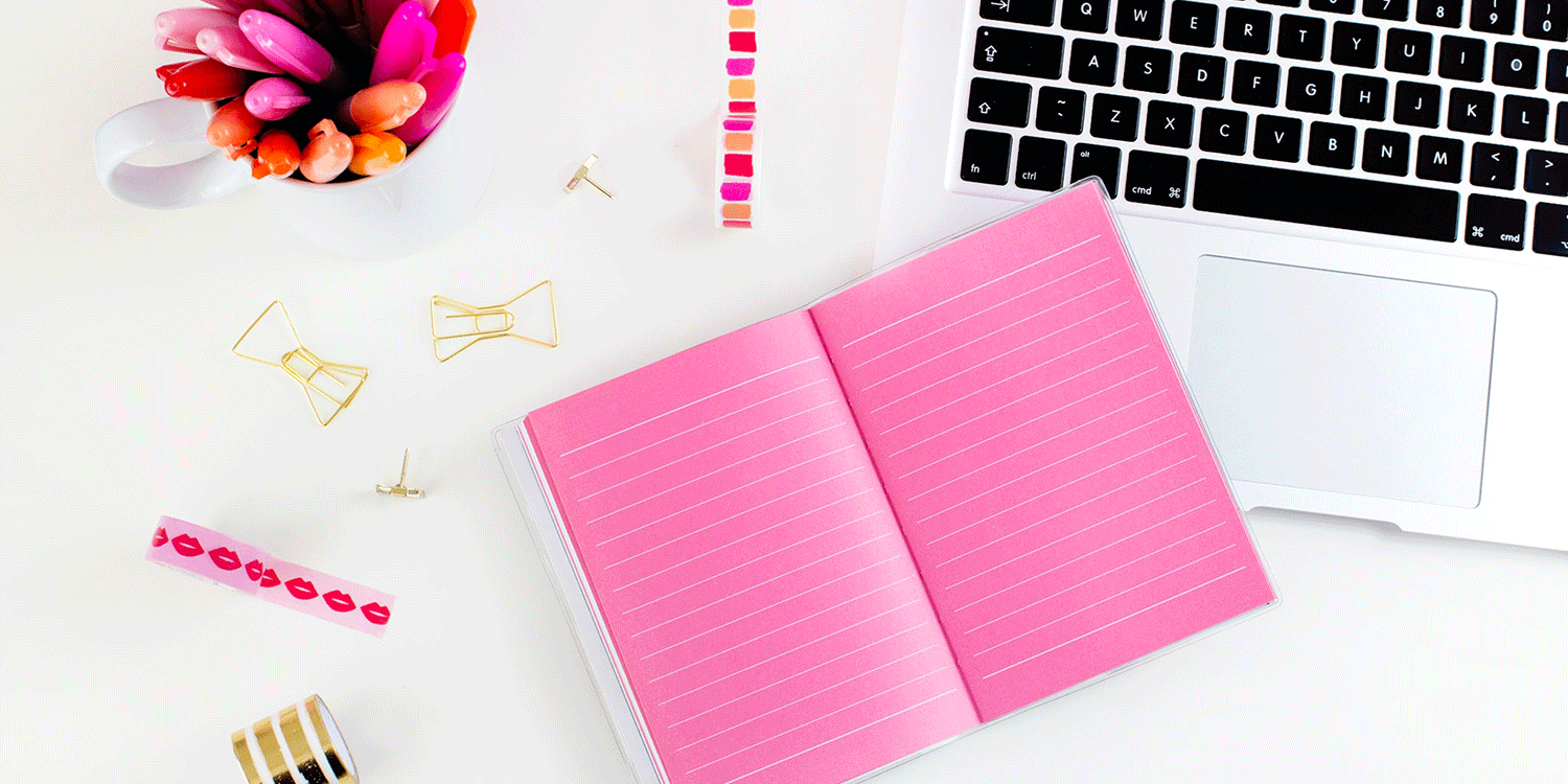 Pink notebook and laptop on desk
