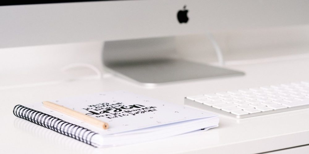 mac computer with journal and pen